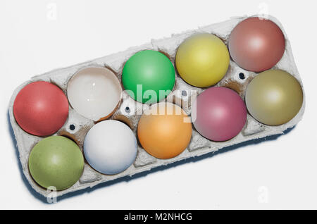 closeup shot with colorful cardboard container with chicken eggs, one is broken, nine eggs painted in different - Stock Photo