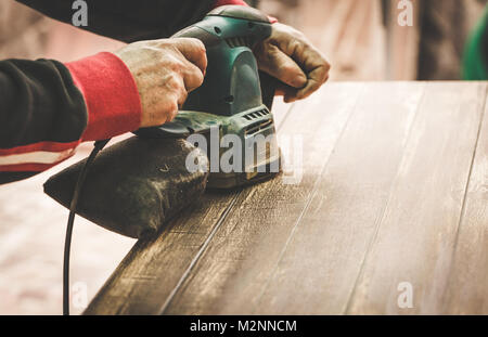 Craftsman hands polishing old color from wooden table with machine. Toned Image. - Stock Photo