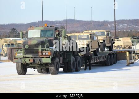 Employees with Equipment Concentration Site-67, a tenant organization at Fort McCoy, load Humvees on to a trailer - Stock Photo