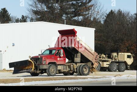 An equipment operator with the Fort McCoy snow removal contractor, Kaiyuh Services LLC of Anchorage, Alaska, places - Stock Photo