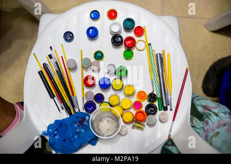 chair with many colourful paint utensils for kids play seen from above - Stock Photo