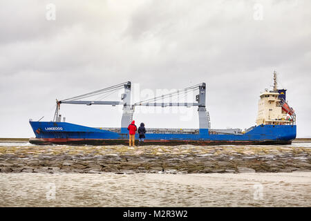 Swinoujscie, Poland - January 28, 2018: People watch Langeoog cargo ship leaving the port of Swinoujscie on a cloudy - Stock Photo