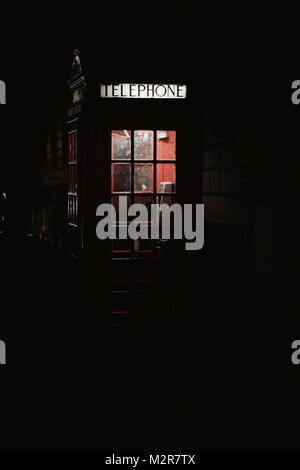 A typical British telephone box at night - Stock Photo