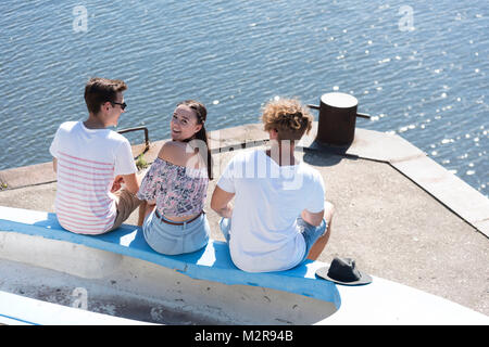 Two young men and a girl sit at the harbour, back view, girl looks into the camera - Stock Photo