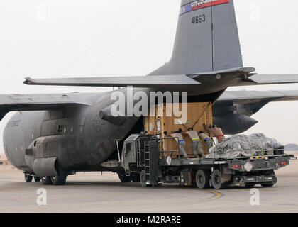 Service members with the 407th Air Expeditionary Group load cargo containers onto a C-130 aircraft on Contingency - Stock Photo