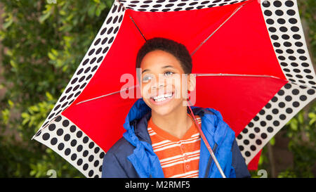 Cute happy African American or black boy holding red umbrella and wearing blue rain coat. Laughing, smiling, boy - Stock Photo