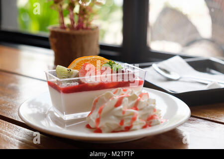 Assorted fruit mousse  cakes with fresh fruit such as grapes, oranges, kiwi and strawberry in coffee shop. - Stock Photo