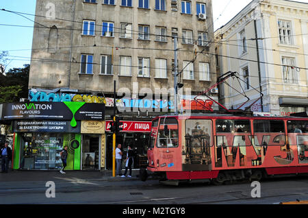 A colourful tram passing a residential building dating back to the pre-1990 Communist era in the centre of Sofia, - Stock Photo