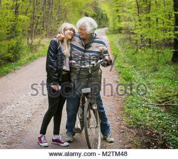 Grandmother and granddaughter embracing on forest road - Stock Photo