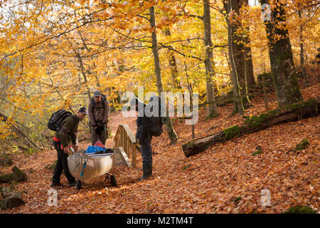 Men carrying kayak through forest in Blekinge, Sweden - Stock Photo