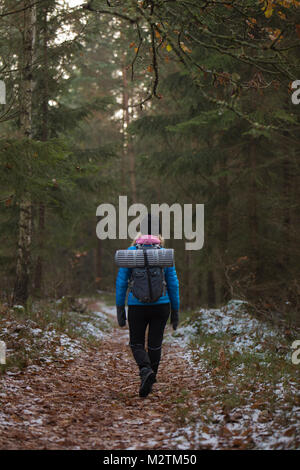 Rear view of woman hiking through forest in Lerum, Sweden - Stock Photo
