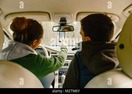 Couple in car getting directions on smart phone in Sodermanland, Sweden - Stock Photo