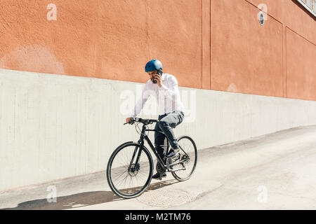 Man on smart phone while bicycling in Sweden - Stock Photo