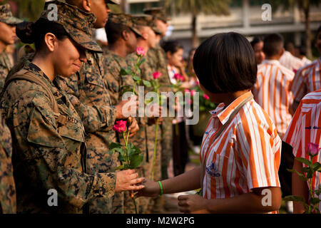 U.S. Marine Corps Lance Cpl. Vanessa Rucio, left, Marine All- Weather Fighter Attack Squadron 242, is handed a rose - Stock Photo