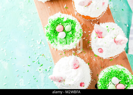Easter cupcakes with bunny ears and candy eggs, copy space top view - Stock Photo
