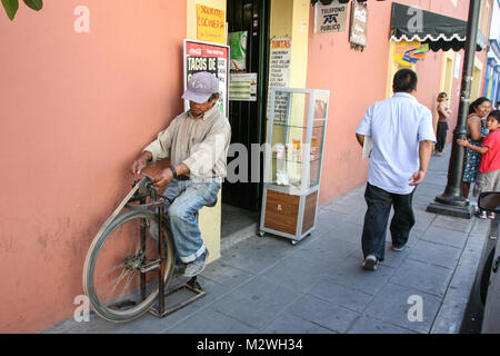 Oaxaca, Mexico - March 7th, 2012: Man grinding knives on a street in  Oaxaca, Mexico - Stock Photo