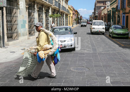 OAXACA, MEXICO - MARCH 7th, 2012: Man selling hand made traditional mexican hammocks on a streets of   Oaxaca, Mexico - Stock Photo