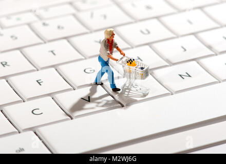 Miniature figurine of a shopper pushing a trolley over a computer keyboard in a concept of online or internet shopping - Stock Photo