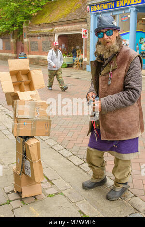 Quirky male character with his home made cardboard sculpture in Canterbury High Street, Kent, UK. - Stock Photo