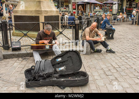 Male street performer playing his guitar in Canterbury, Kent, UK - Stock Photo