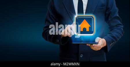 The house is in the hands of the businessman  home icon or symbol - Stock Photo