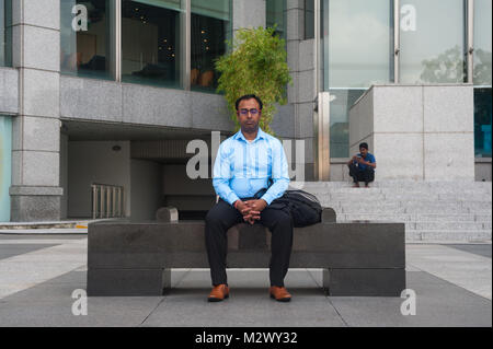 21.12.2017, Singapore, Republic of Singapore, Asia - An office worker takes a break on a bench at Boat Quay in Singapore's - Stock Photo