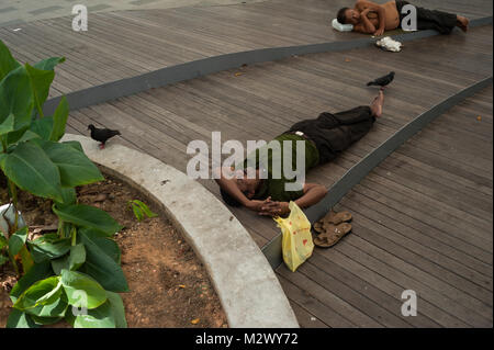 31.01.2018, Singapore, Republic of Singapore, Asia - Two men are taking an afternoon nap on a pedestrian bridge - Stock Photo