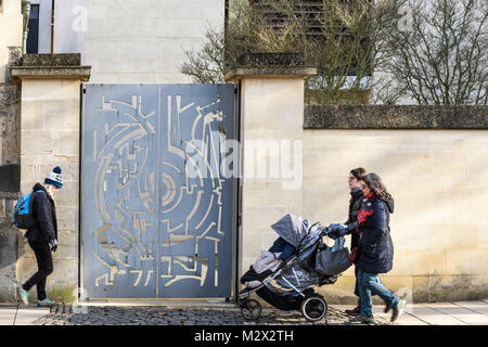 Passers-by on St Giles road in front orf the metalwork patterned gate to the Barn gallery of St John's college at the university in the city of Oxford