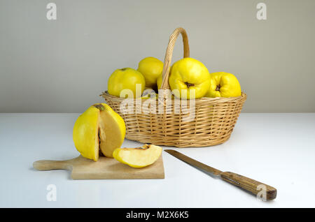 Composition of basket of quinces on a white table - Stock Photo