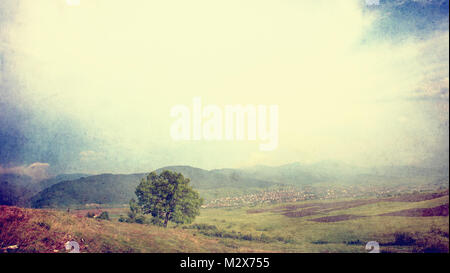 vintage textured and filtered rural sunset scene with a small village hiding on the mountain, alone tree in foreground - Stock Photo