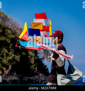 Bali, August 31, 2013: Balinese boy sells kites on the Bali beach - Stock Photo