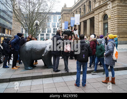 tourist crowd gathering around the bull and bear sculpture in front of historic Frankfurt Stock Exchange building - Stock Photo