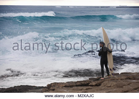 Surfer with surfboard standing on rocks wearing wetsuit watching ocean - Stock Photo