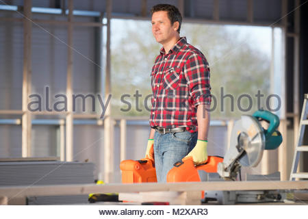 Carpenter workman carrying tools on indoor building construction site - Stock Photo