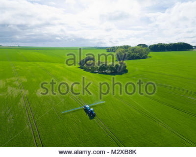Aerial view of tractor spraying crop in green farm fields with pesticide - Stock Photo