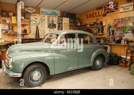 Old Green Morris Oxford inside an old garage in Northumberland UK - Stock Photo