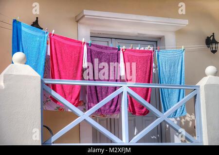 Hermoupolis: February 8 . Towels drying on balcony in the sun. Hermoupolis February 8 2018. Syros Greece. - Stock Photo