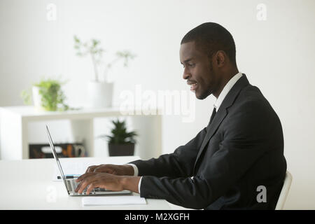 African-american attractive businessman in suit working on laptop in office, happy black ceo looking at computer - Stock Photo