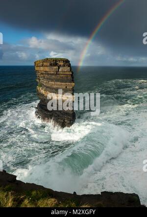 Rainbow and storm waves surround Dun Briste seastack, Downpatrick Head, County Mayo, Ireland. - Stock Photo