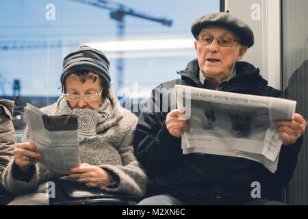 Elderly couple reading the newspaper on the S-Bahn, Berlin. - Stock Photo