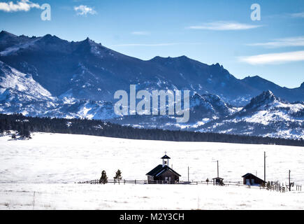 A small log country church nestled in a valley surrounded by tall rocky mountains in a Wyoming countryside landscape - Stock Photo