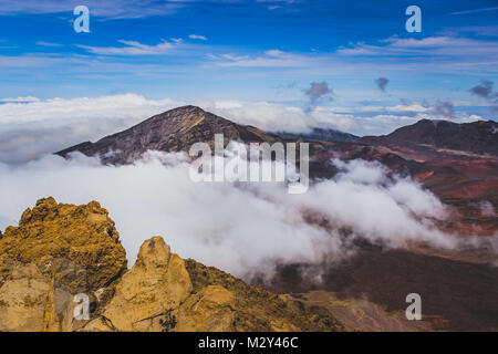 Colorful view of volcanic cones and clouds covering the peak of Haleakala Crater in Maui, Hawaii - Stock Photo