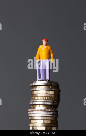 Pension concept. Old person figure on a stack of coins - Stock Photo