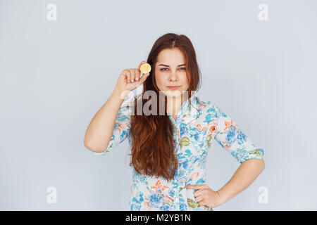 Young confident woman holds a gold bitcoin in her hand - Stock Photo