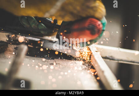 Craftsman sawing metal with disk angle grinder in a warehouse. - Stock Photo