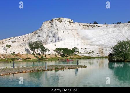 Lake and calcified limestone terraces on background, Pamukkale, Turkey - Stock Photo