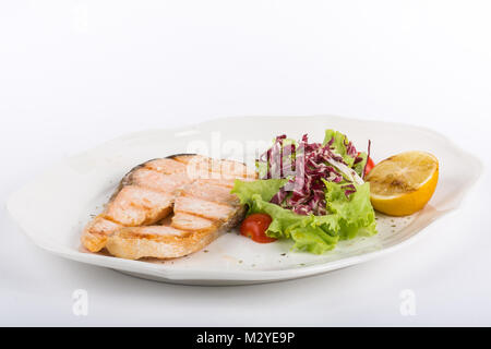 fried salmon steak with salad and lemon on a white plate isolate - Stock Photo