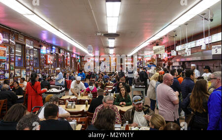 Customers and servers wait staff in the busy, crowded dining room at Katz's Delicatessen, a famous New York City - Stock Photo
