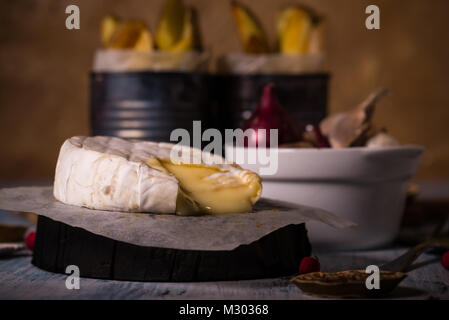 Horizontal photo with whole grilled camambert cheese. Small triangle piece is cut off and melted cheese is floating - Stock Photo