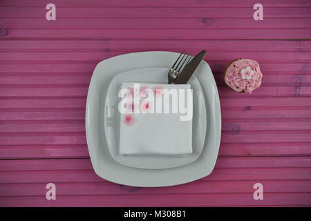 Easter time table place setting in white with cupcake and Easter egg decorations - Stock Photo